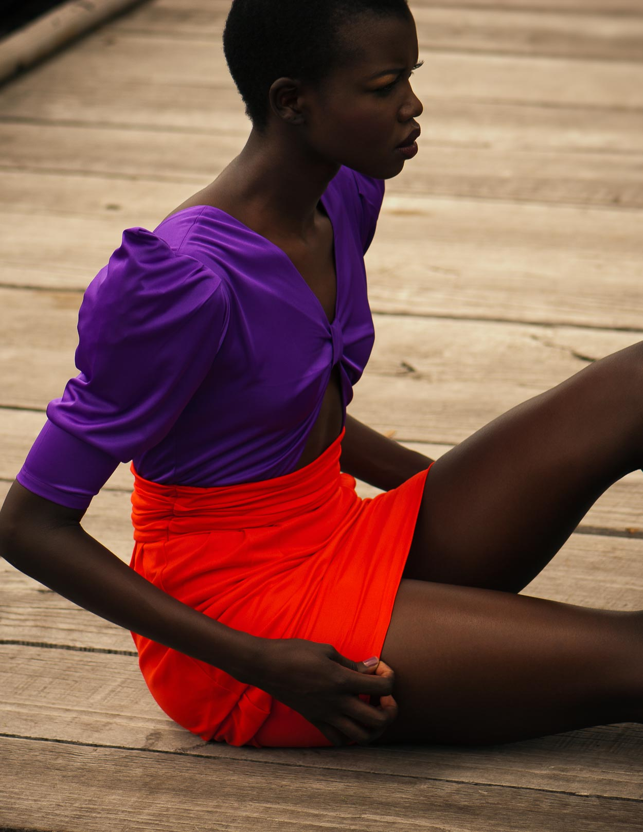 A black fashion model wearing neon orange designer skirt and a neon purple top sitting on a deck along the FDR in New York